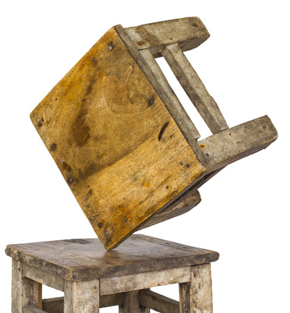equilibrium: Isolates two small wooden chairs, which overturned and laid the corner were not unstable equilibrium. Stock Photo