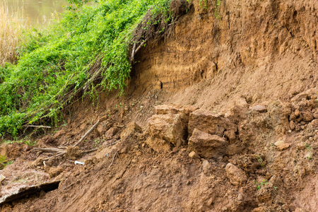 land slide: Sectional layer of underground water slides down due to erosion of the river is covered with grass. Stock Photo