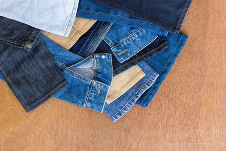 distal: Background rag distal leg jeans plenty left over from sewing stacked on a wooden floor.