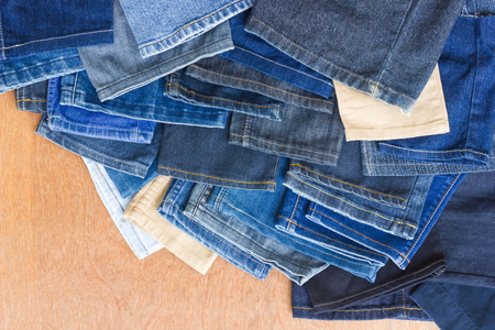distal: Antecedentes de trapo distal jeans de pierna mont�n queda de cosiendo apilados sobre un suelo de madera.
