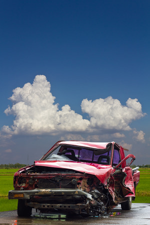 fender bender: Red car accident which destroyed parked on a paved surface, wet rice fields near the cloud sky as a backdrop. Stock Photo