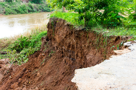 Damage to the broken slabs under the road alongside the river, which eroded landslide erosion. Stock Photo