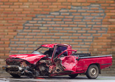 Old red pickup truck was demolished by the front left side of a brick wall as a backdrop for the incident.