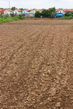 tillage: Background agricultural soil tillage, preparation for planting, which is located in a housing estate. Stock Photo
