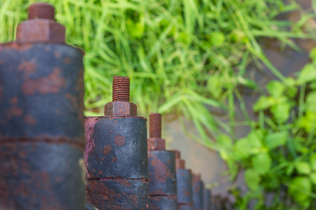 bolts and nuts: Close-up view from above, bolts, screws, rust-focus blur that line the water and grass in the background. Stock Photo