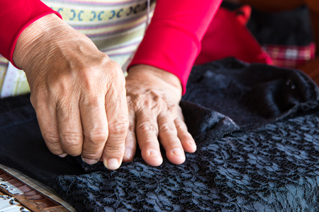 mend: Close up of an elderly woman who was to mend the fabric with black flower pattern sewing older.