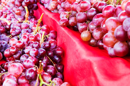 coverings: Pile a bunch of purple grapes, fruit on the table, which has many beautiful red cloth coverings are to be sold.
