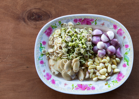 Spicy salad with spices such as galangal, lemongrass, onion and garlic pieces are placed in a dish. Stock Photo