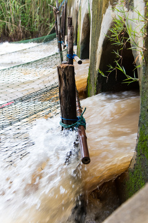 waterfall  dirty: Rushing water flowing strongly through out the concrete pipe, which has a large fishing net. Stock Photo