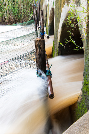 rushing water: Rushing water flowing strongly through out the concrete pipe, which has a large fishing net. Stock Photo