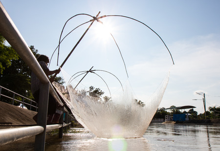 ploy: Close-backlit am flattered fishermen fishing in the canal water, which has a steel fence barrier. Stock Photo
