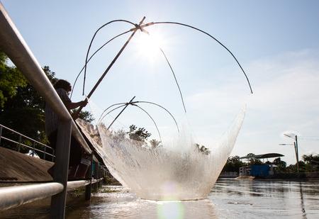 Close-backlit ben gevleid vissers vissen in het kanaal water, waarin een stalen hek barrière heeft. Stockfoto