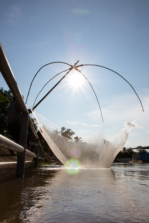 Close-backlit am flattered fishermen fishing in the canal water, which has a steel fence barrier. Stock Photo