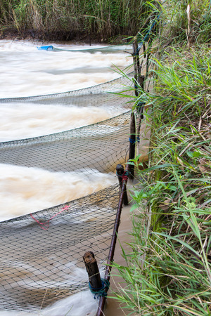 traps: Nylon mesh numerous floating and submerged in the water flow out of the concrete pipe traps to catch fish.