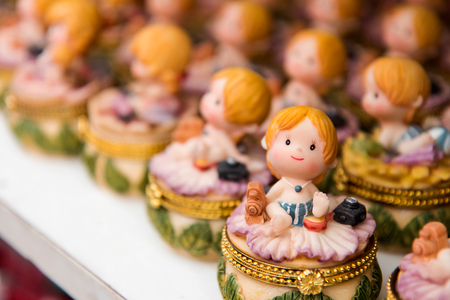lined up: Ceramic doll small girl sitting in a row lined up waiting to sell many beautifully.