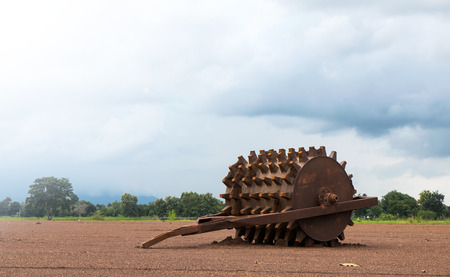 Steel wheels, a piece of rollers abandoned gravel laid on the ground in rural Thailand agriculture.