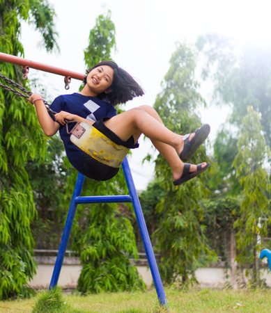nightmarish: Thailand young girl sitting on a swing chains, steel beams and swinging away merrily in the park.
