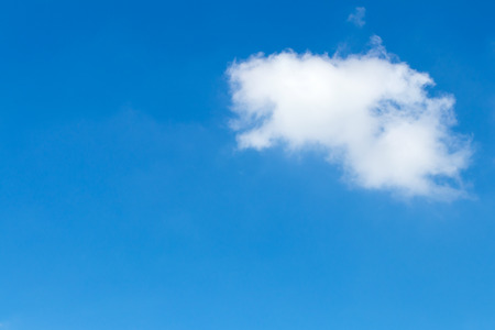 Background with soft white clouds floating above blue sky alone.