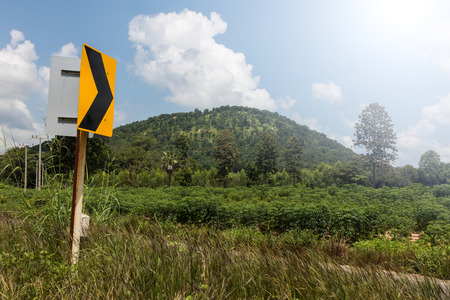Close signpost bends on the roadside grass and cloudy sky with mountains in the background. Stock Photo