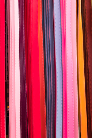 ranging: Close background belt bright colors ranging hung up for sale in a shop somewhere.