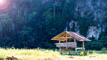Wooden shacks and rusted old tin roof is weathered, worn with large cliff as a backdrop.