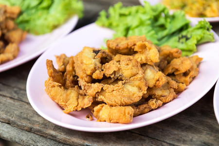 bagre: Close-fried crispy fish pieces on a plate heaped with old wooden floors appetizing.