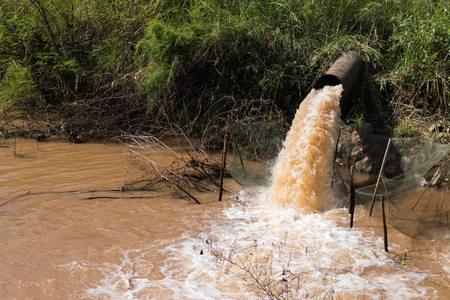 Close up of water gushing from the sewer to the coop in rural canals which flow stops recording. Stock Photo