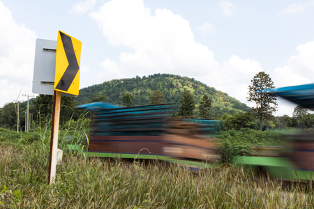 Mini-tractor trucks passing blur of farmers are rapidly approaching signs curve slopes. Stock Photo