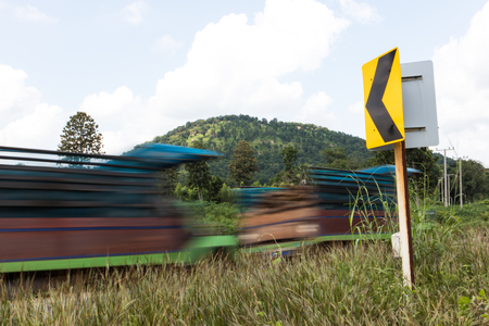 rapidly: Mini-tractor trucks passing blur of farmers are rapidly approaching signs curve slopes. Stock Photo