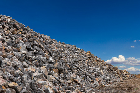 Large piles of granite boulders and lots of small, high heaps with a sky as a backdrop. Stock Photo