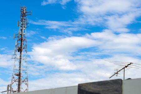 Telecommunications mast with an antenna on the roof of the cloudy sky as a backdrop. Stock Photo