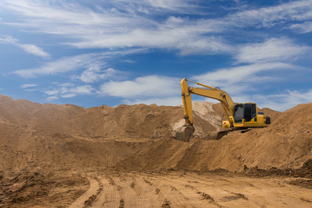 Backhoe on a pile of large sandstone which traces the wheels beneath a cloudy sky as a backdrop.