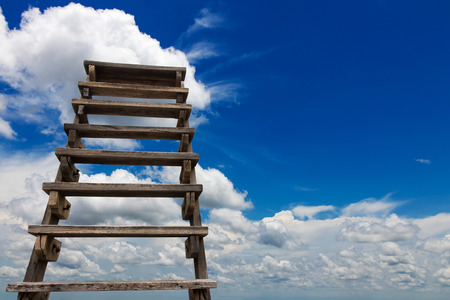 View from the lower old wooden staircase which leads up to the heavens with clouds on the sky as a backdrop.