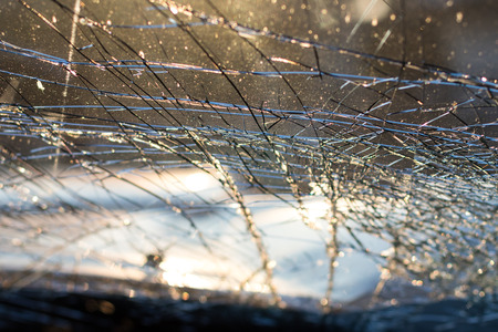 Close-up details of the inside of the windshield is cracked due to an accident with another vehicle, severely.
