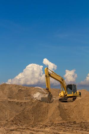 cargador frontal: Retroexcavadora sobre una pila de piedra arenisca grande que traza las ruedas debajo de un cielo nublado como telón de fondo.