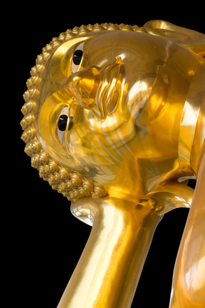 Close-up isolate, lower corner, large statue of Buddha face, which is sleeping arm-hand conscious.