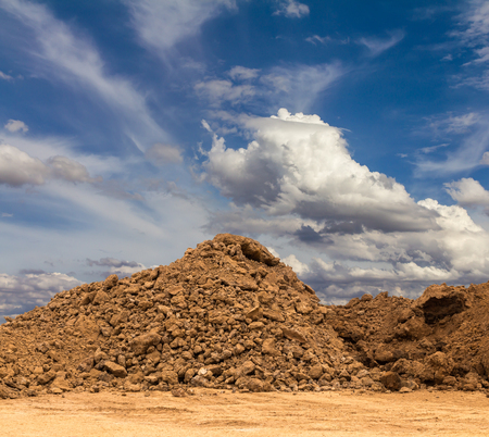 A group of sand dirt on the ground, which was dug up with a backdrop of clouded sky.