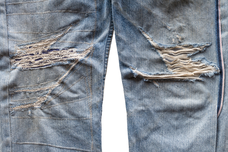 Close-up background, leg surface, torn old jeans, which have been sewn repaired. Stock Photo
