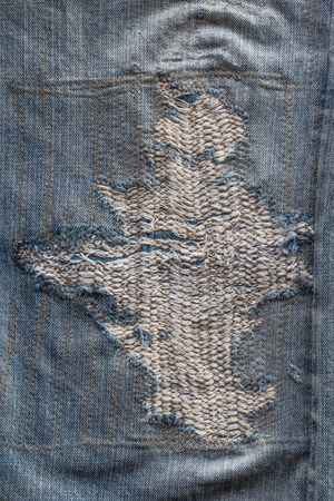 Close-up background, textured surface, torn jeans, repaired with craftsmanship and art. Stock Photo