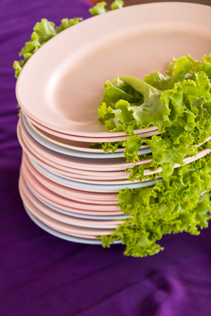 Close-up picture of green lettuce, which is placed in a stacked overlap with purple cloth, supports the table. Banco de Imagens