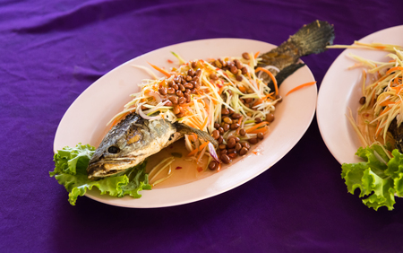 striped snakehead fish: Fried fish, sprinkled with peanuts and mango chopped on a plate, placed on a delicious purple cloth.