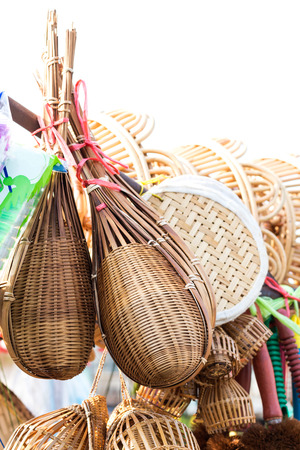 basketry: Many Thai handicrafts are hung on wooden rails for sale in a market. Stock Photo