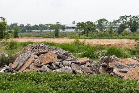 pile dwelling: A pile of concrete debris on the ground, covered with grass, near the village dwelling.