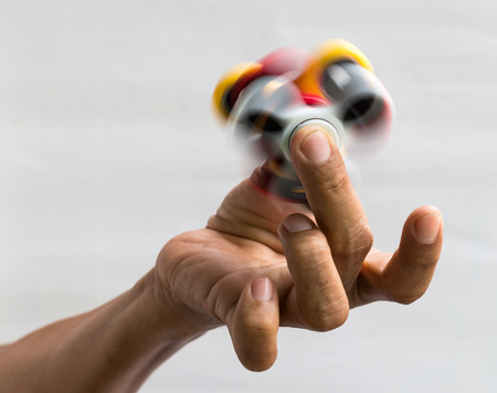 Isolate Thai finger man holding a spinning red spinner with a spinning yellow color which is a popular toy.