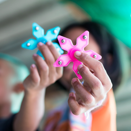 Close-up image of hand spinner, which is a popular toy in the hands of a boy with a girl blurred as a backdrop. Stock Photo