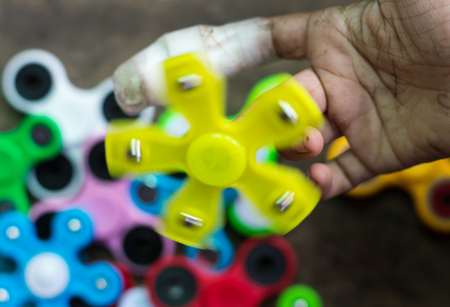 Close-up shot of a yellow spinner spinning on the hands of a wounded child with many different colors.