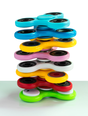 Spinners are a variety of colors that overlap with balance on a white background. Zdjęcie Seryjne - 81607763