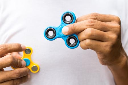 Imagen de primer plano de un spinner azul en la mano izquierda con el otro en la mano derecha.