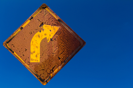 Close-signposted right turn yellow and black weathered old rusty clouds on the sky. Stock Photo