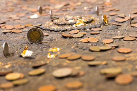 Close-baht coins blurred many old pile upright on a platform Footprint in the ancient temple.